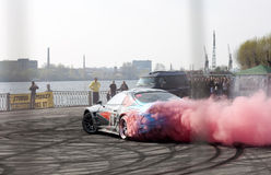 Car drifting with red smoke at Royal Auto Show. Royal Auto Show 2013. Russia St. Petersburg. May 10th Stock Photo