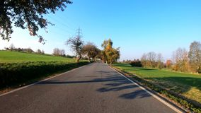 Car drive in Autumn with fall colored trees. Car drive in autumn landscape with fall colored trees and blue sky in sunny day. Countryside road. Fall concept stock video