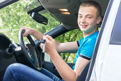 Car driver. Caucasian teen boy showing car key in the new car. Royalty Free Stock Photos