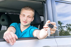 Car driver. Caucasian teen boy showing car key in the new car. royalty free stock images