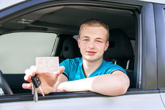 Car driver. Caucasian teen boy showing driver license, new car k Stock Photos