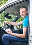 Car driver. Caucasian teen boy showing driver license in the new Stock Images