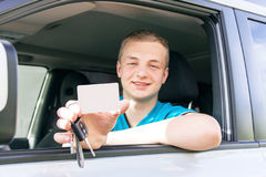 Car driver. Caucasian teen boy showing an empty white card, car Stock Images