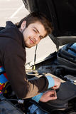Car driver examining the car's engine Royalty Free Stock Photo