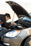 Car driver examining the car's engine Royalty Free Stock Images