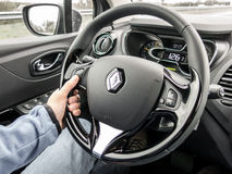 Car driver hand on the wheel on cruise control driving Royalty Free Stock Image
