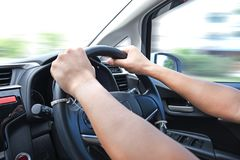 Car driver hands on the steering wheel driving a car with motion. Blur background royalty free stock photos