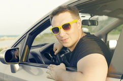 Car driver happy. Young man in a car smiling in yellow sunglasses Royalty Free Stock Images