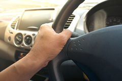 Car driver keeps driving wheel one hands. Royalty Free Stock Image