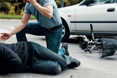 Car driver making emergency call after collision with a cyclist. On the street royalty free stock photography