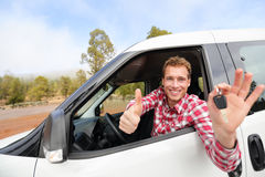 Car driver showing car keys and thumbs up happy. Young man holding car keys for new car. Rental cars or drivers licence concept with male driving in beautiful Stock Photos