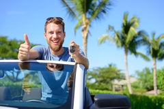 Car driver showing keys and thumbs up happy. Young man holding car key for new leasing convertible. Rental cars or drivers licence concept with male driving Stock Images