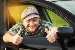 Car driver shows that all is well. Happy car driver shows that all is well stock photography