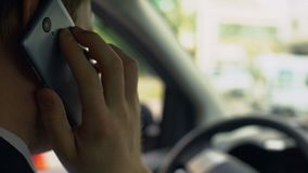 Car driver talking on cellphone with client, sitting in auto, callback, busy day. Stock footage stock footage