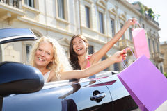 Car driver woman driving and shopping with friends. Car driver women driving and shopping with girl friends holding shopping bags happy and excited on road trip Royalty Free Stock Photos