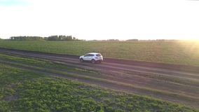 Car drives along ground road past fields at bright sunset. White car drives slowly along narrow ground road past green fields against forest on horizon and stock video