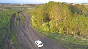 Car drives along winding ground road to small blue lake. White car drives along winding ground road going around small tree grove to blue lake against lively stock footage