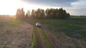 Car drives along winding road past cluster of green trees. Small white car drives along winding road past little cluster of green trees at sunset under dark stock footage