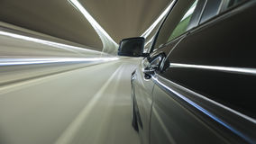 Car drives through a city tunnel during night, streaking tunnel lights Royalty Free Stock Photos