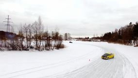 Car drives by icy track on snow covered lake at winter. Aerial view. Sport car racing on snow race track in winter stock images