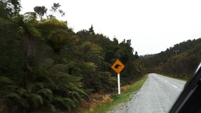 Car drives past a kiwi road sign in nz. A car drives past a kiwi road sign in new zealand royalty free stock photography