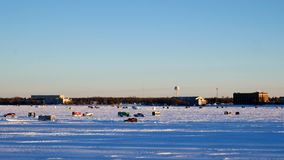 Car drives past Winter Fishing Houses on frozen Lake Bemidji in Minnesota. Car drives past Winter Fishing Houses on frozen Lake Bemidji in Minnesota on a late stock footage
