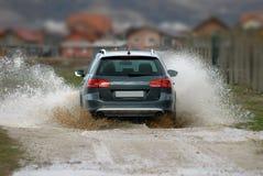 Car drives through water. Car drives through flooded road Stock Photos