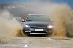 Car drives through water Royalty Free Stock Photos