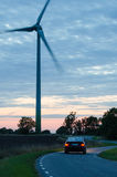 Car drives at a winding road with a wind turbine at roadside Royalty Free Stock Photos