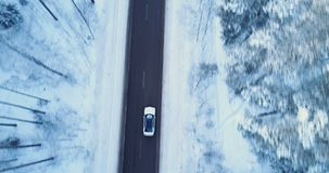Car drives on a winter road. Winter road, trees and bushes covered with snow. Aerial view of a snowy forest with high pines and road with a car in the winter stock video footage