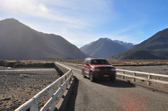 Car driving across single-lane bridge in New Zealand Stock Images