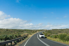 Car driving along curving coastal road on sunny day. Modern car driving down a curving coastal road with blue skies and clouds Stock Images