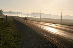 Car driving along foggy road Royalty Free Stock Photos