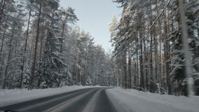 Car driving along the forest road in winter. Driving POV on snowy country road. Snow covered road stock footage