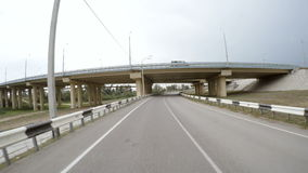 The car is driving along the highway. Rear view. The car is driving along an empty road passing under the bridge. On the bridge there is a high speed highway stock footage