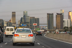 Car driving along highway towards urban city centre. A number of cars driving along a busy highway towards the downtown urban centre of a large city. tall Royalty Free Stock Image