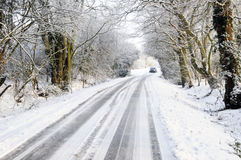 Car driving along snow covered country lane Stock Photography