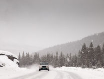 Car driving along snow covered road in a snowstorm Royalty Free Stock Images