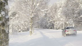 A car driving along the thick snow street. The cars has snow on the back and the trees covered with snow on the side of the road stock footage