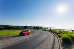 Car driving on the asphalt curvy road through green fields and forests on a sunny day in Normandy, France. Countryside. Landscape, sunbeams in the blue sky Stock Photo