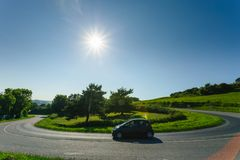 Car driving on the asphalt curvy road through green fields and forests on a sunny day in Normandy, France. Countryside. Landscape, sunbeams in the blue sky Royalty Free Stock Photography