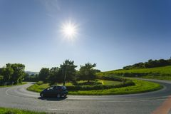 Car driving on the asphalt curvy road through green fields and forests on a sunny day in Normandy, France. Countryside. Landscape, sunbeams in the blue sky Stock Photos