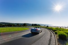 Car driving on the asphalt curvy road through green fields and forests on a sunny day in Normandy, France. Countryside. Landscape, sunbeams in the blue sky Stock Image