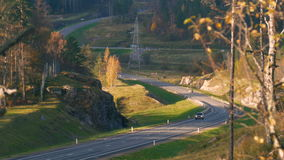 Car driving on an asphalt road in the autumn forest. This road with sharp turns, it is located in Karelia. Russia, 2016 stock footage
