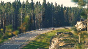 Car driving on an asphalt road in the autumn forest stock video footage