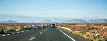 Car driving away to mountains in Canary Island desert Royalty Free Stock Photography