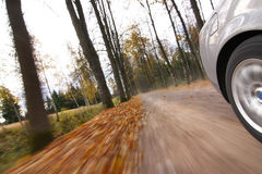 Car driving on country road. Autumn scene, low angle, motion blur Stock Photography
