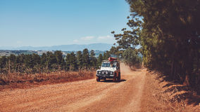 Car driving on country road with canoe on top Royalty Free Stock Photography