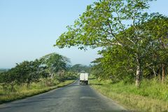 Regional road in Cuba with green trees around. A car driving on country road with green trees around in Cuba royalty free stock photos