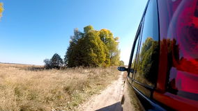 Car driving through the countryside. The camera is left outside. Beautiful reflection on the car body stock video